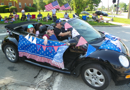 Car with flags in parade