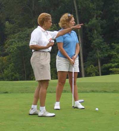 Barbara Danforth instructing a woman at the YWCA- Ohio Womens Bar Association Golf Outing