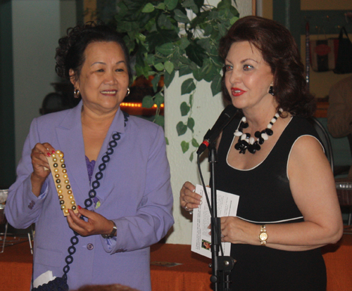 Gia Hoa Ryan holds a piece of jewelry that Maria Pujana offered to auction off for the International Services Center