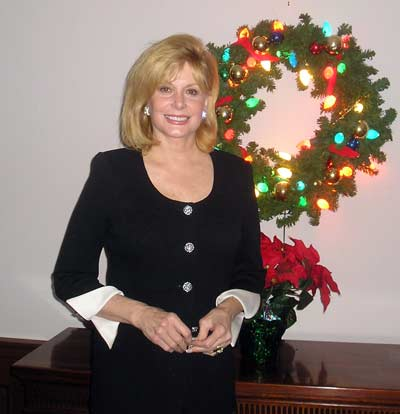 Wilma Smith in front of Christmas wreath